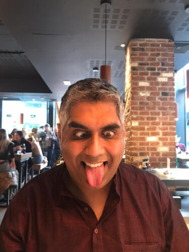 photo of a man head faced towards the camera with eyes crossed and tongue out