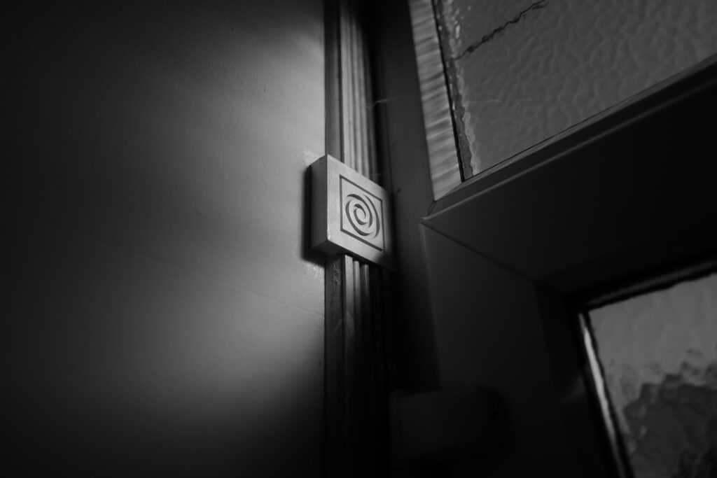 A black and white phot of sunlight hitting a piece of architrave through a window