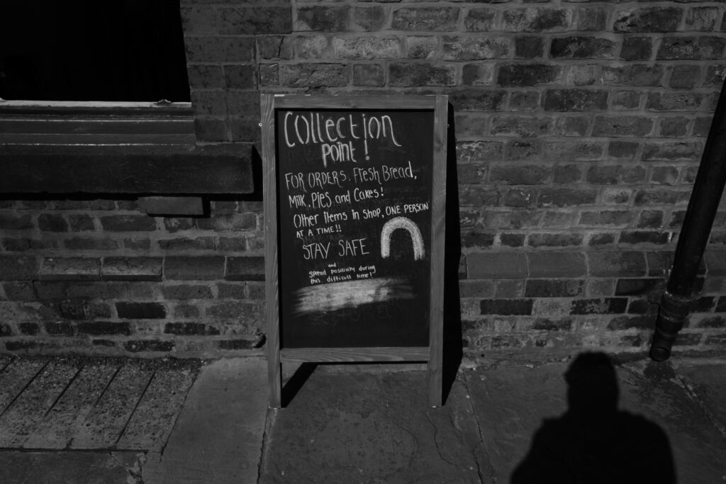 An a-frame chalboard propped up against a wall advertising fresh bread, milk and pies for collection