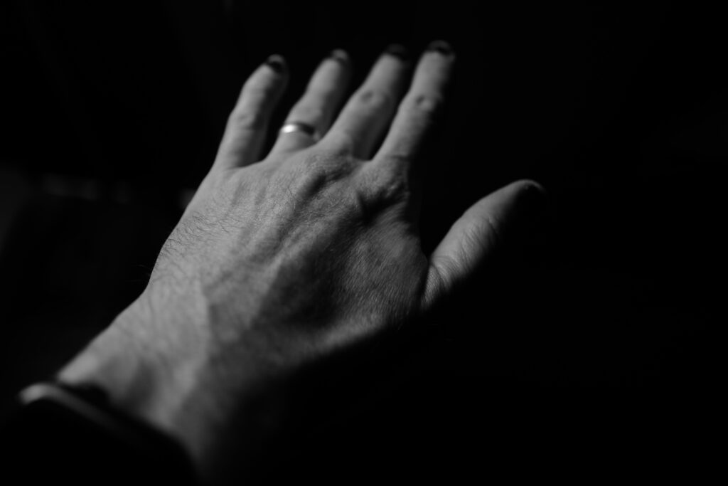 Back of a man's hand, which looks quite wrinkled and has a gold wedding band