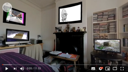 A still from the artwork,the inside of a bedroom with a black fireplace centrally with a screen above. To the right is a TV on a stand in front of a book case and to the left a computer monitor on a worktop with another screen above on the wall.