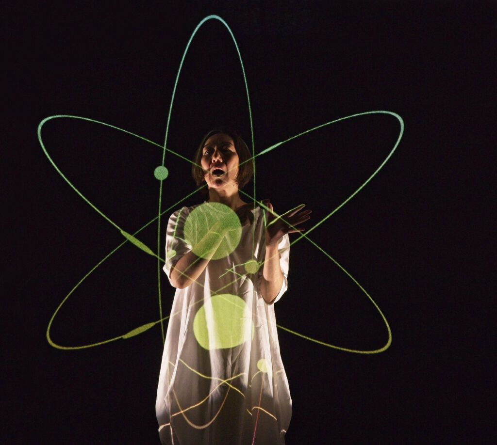 Japanese woman with picture of atomic isotope projected in front of her body