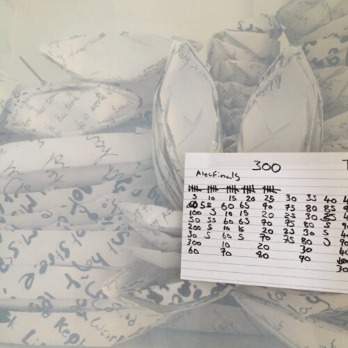 origami boats made with white paper featuring illegible handwritten text viewed through the slightly frosted wall of a perspex box. A handwritten note with numbers counting up in fives to 300 is stuck on the outside of the box