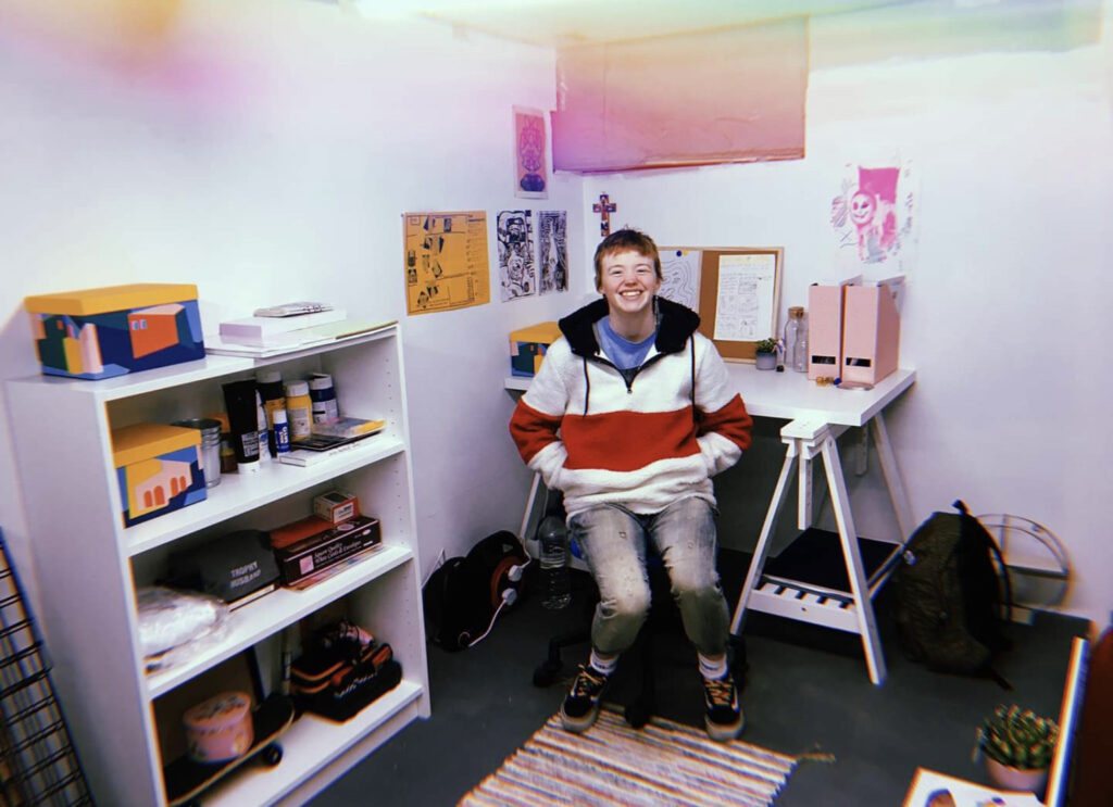 Leo, a white man with short brown hair, sits facing the camera in front of his desk, on the left there is a bookshelf with a lot of art supplies. On the wall behind him is some original artwork and art from friends.