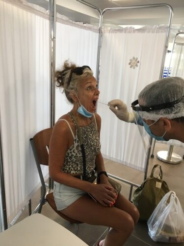 photo of a womn being tested with a swab being inserted into her mouth and screens around her