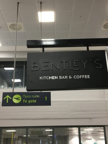 photo of a sign for a kitchen bar hanging from an airport ceiling