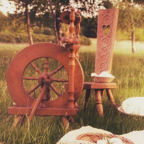 A yarn spinning wheel and intricately carved chair in a field
