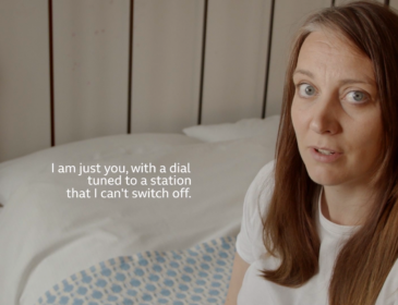 A woman sitting on a bed talking directly to camera. Written captions beside her read 'I am just you, with a dial tuned to a station that I can't switch off'.