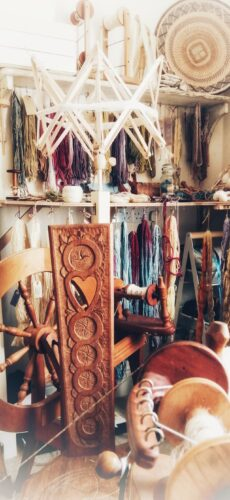 A cluttered workspace with an old wooden loom and lots of threads of coloured yarn hanging up