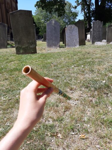 a light skinned hand holds a wooden flute in front of the camera. Behind it gravestones on dry grass.