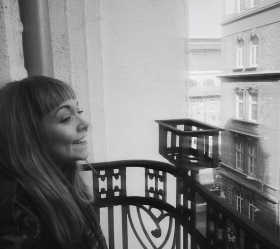 This is a black and white photo of Rose Sergent. It is a photo of her from the side, she is looking to the right and laughing. Her hair is long and she has a fringe. She is stood on a balcony, across from her is a large block of flats.