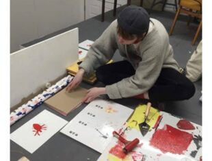 Leo sits on the floor of his studio making prints. On the floor beside him is a canvas with ink rolled out onto it. He is rolling the ink onto cut bits of lino and printing it onto paper.
