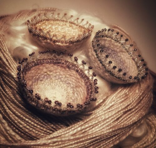 3 tiny woven baskets with intricate beads around the edges