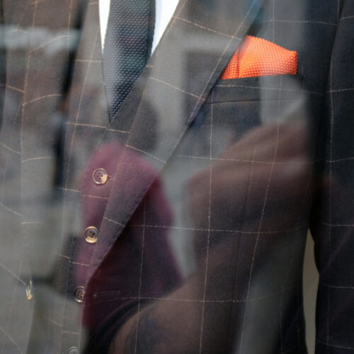 Photograph of a posh suit shot through a shop window, you can see the reflection of the hand of the person taking th ephotograph
