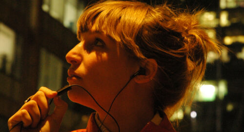 A white woman speaks into a microphone on her headphones. She is outdoors in the city at night.
