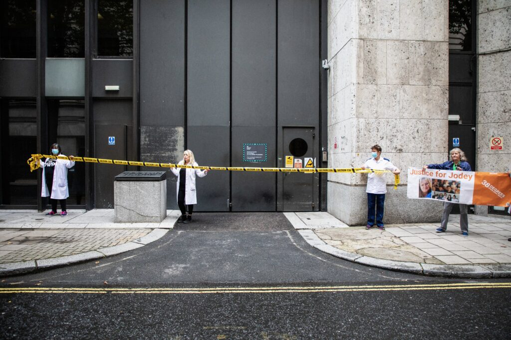 a group of artist, activists draw a tape across the entrance to the DWP