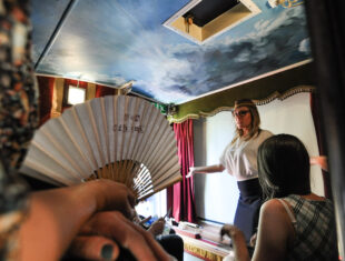 White woman with blonde hair performs to a small audience in a caravan, a person holding a paper fan can be seen in the foreground
