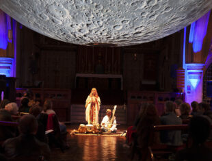 a white woman and an indian man are centre stage below a large suspended depiction of the moon