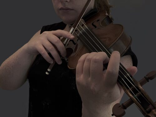 photo of hands holding a bow across a violin
