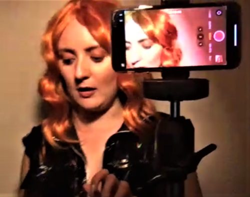 portrait of actress posing in costume with second image on phone camera off to the side