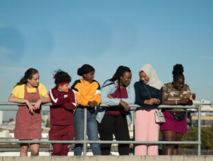 Six teenage girls including Rocks stand side-by-side, talking and smiling.