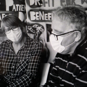 black and white still of a man and a woman wearing face masks
