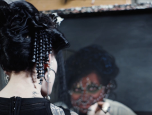 A white woman with black hair painting an oil portrait of a heavily pierced and tattooed woman
