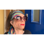 Liz Carr is playing Zsa Zsa. She is seated in her wheelchair at an open front door. She is wearing a long thin, chic, colourful headscarf over a bob hairstyle. She is wearing large sunglasses and red lipstick and is giving the camera the side eye.