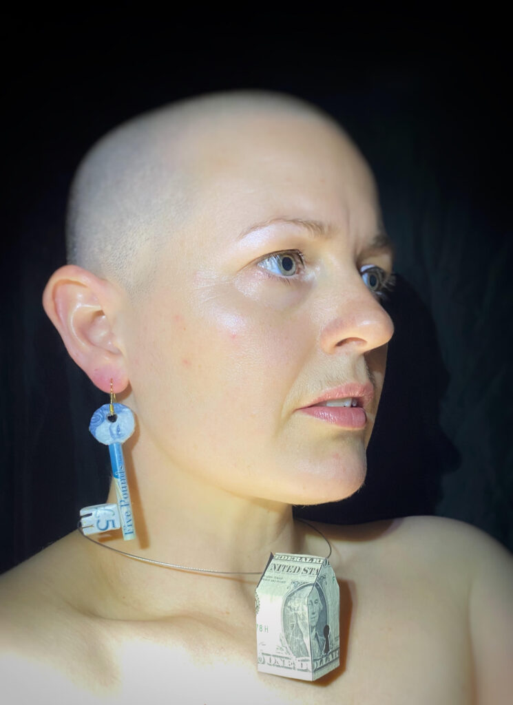 headshot of an artist wearing a sculpted key from their right ear