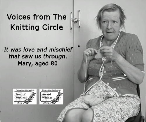 Still from the film showing former resident, Nan, in a kitchen. She rocks, poking out her tongue, as she knits. Nan is played by Penelope Freeman. Black text over the image reads: Voices from The Knitting Circle. It was love and mischief that saw us through. Mary, aged 80.