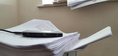 A pile of paper on a printer with more paper coming out of the printer and even more paper in the background.