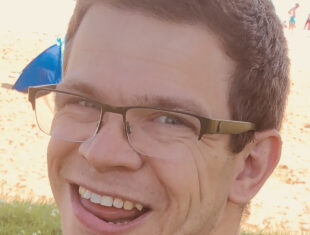 Photograph of a white man with glassses and short brown hair smiling
