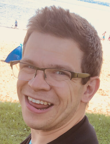 Photograph of a white man with glasses and short brown hair smiling
