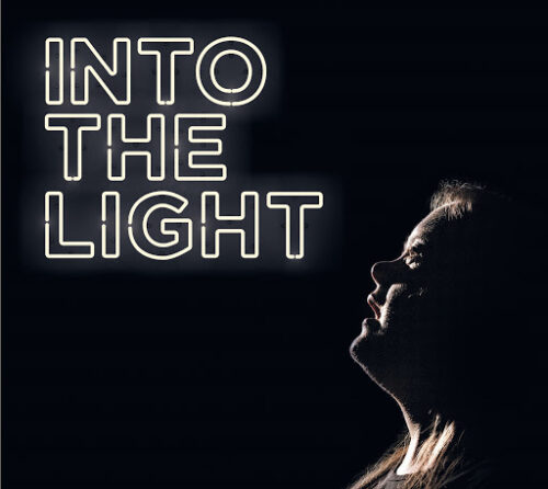promo flyer for Into the Light, showing a woman looking up at the title in white capitals against a dark background