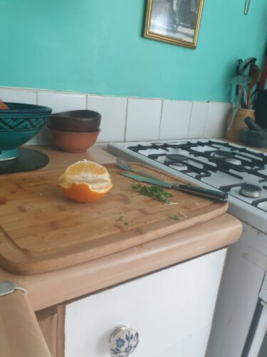 A kitchen hob and a chopping board with orange and herbs on it
