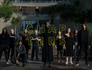 Ten Guildhall School students standing or kneeling in formation outside at the Barbican estate, surrounded by concrete and trees, with the word 'CHAPTERS' overlayed on the image in yellow outline