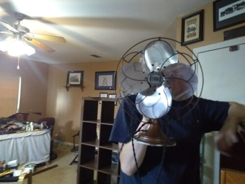 A person holding an electric fan in front of their face