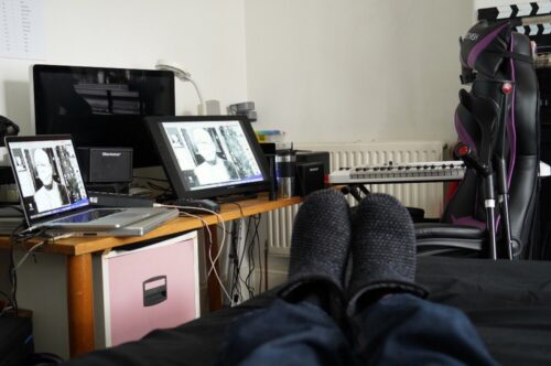 Photograph taken from a bed showing a desk with lots of equipment and the photographers feet