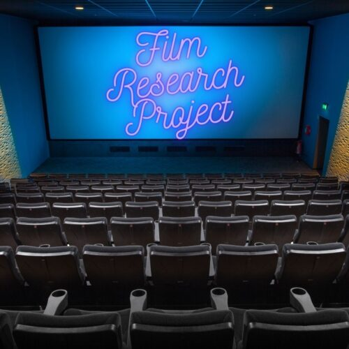 "Brown empty cinema seats look down to a white screen with the words ""Film Research Project"" in script writing scrawled on the screen."