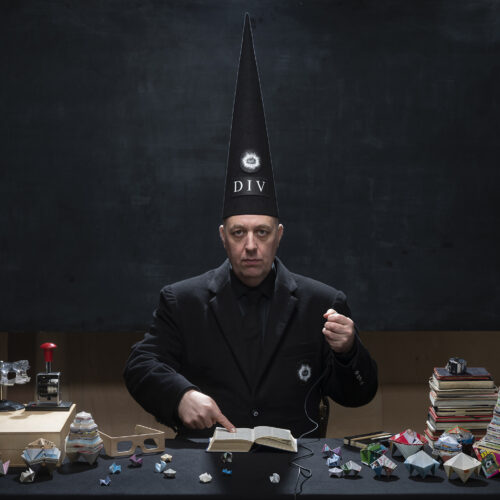 White man in a black suit and large conical dunce hat pointing at a book