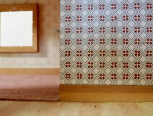 Domestic scene of a wallpapered wall, pink carpet and blank picture frame on the wall