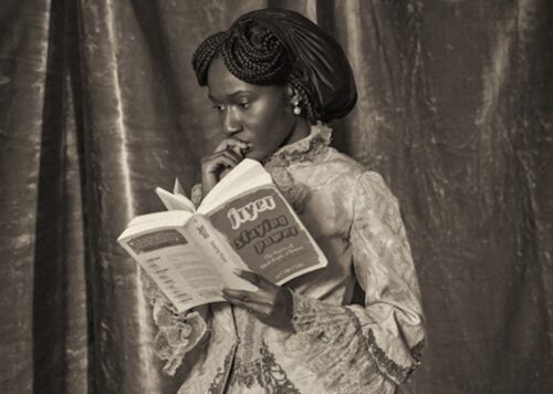 Image of young black woman reading a book, wearing a long old fashioned dress.