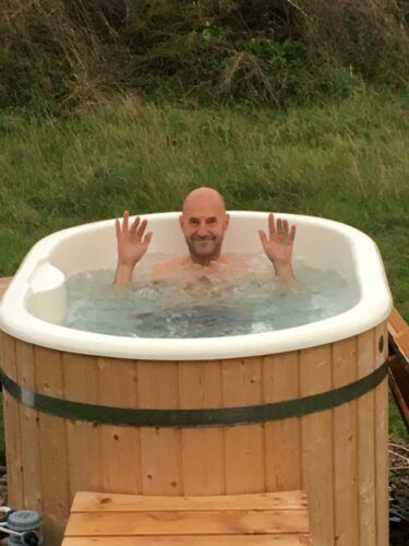 A white bald man with a beard in a outdoor hot tub waving