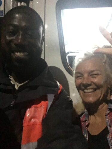 Black man in Tesco delivery uniform with a white woman in her 50s, standing in front of his van, smiling