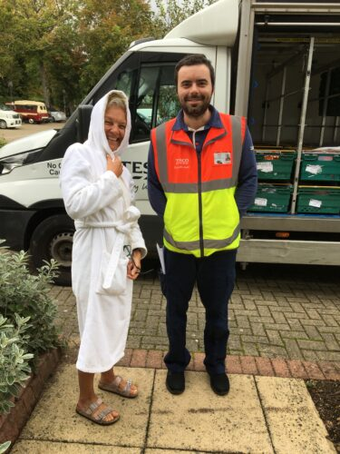 White Tesco delivery man standing next to a white woman in her 50s in a dressing gown