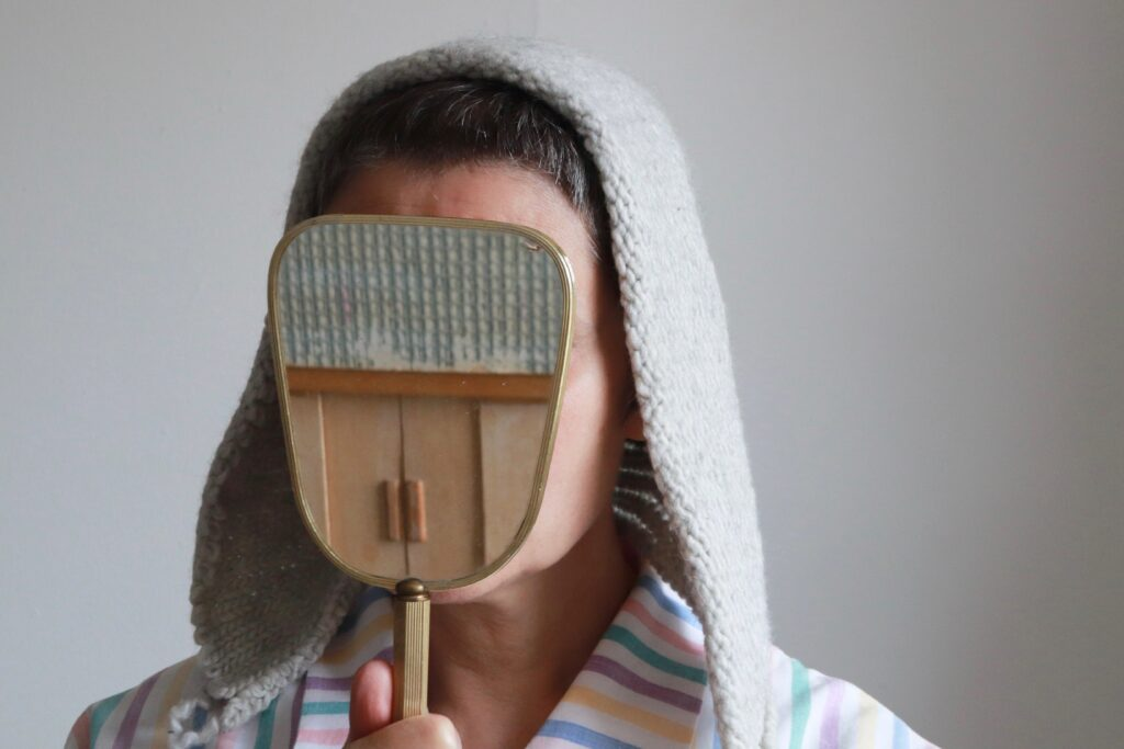 A white woman holding a mirror up against her face