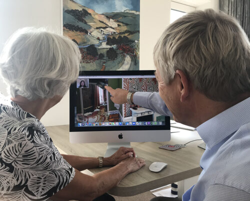 Two people sat at a table in front of a computer screen, one of them points at the screen which is displaying a virtual tour of a house.