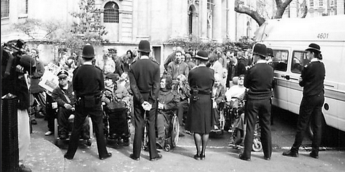 A black and white photo of a group of disabled people protesting, a line of policemen and women stand in front of them with their backs to the camera.