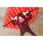 A woman looking surprised is dressed in a black jumpsuit with pink lips prints on, a mouth-shaped pink plastic bag is resting on her chin, she is lying on a big inflatable red mouth with her arms up.