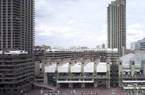 A photo of the Barbican taken from the Lakeside Terrace showing the building with the residential towers in the background